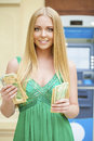 Blonde woman in a green dress is holding a cash dollars Royalty Free Stock Photo