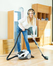 Blonde woman in headphones cleaning with vacuum cleaner happy on parquet floor at home Stock Photography