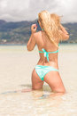 Blonde woman on her knees at the beach sexy back of a beautiful in shallow water Stock Photos