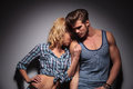 Blonde woman kissing her lover on shoulder women his studio shot Stock Photography