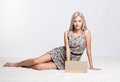 Blonde woman with laptop young sitting on white whole floor carpet browsing Stock Photography