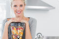 Blonde woman leaning on her juicer and smiling at camera home in kitchen Royalty Free Stock Photography
