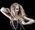 Blonde woman with long hair and a pearl beads on dark background beautiful young Royalty Free Stock Images