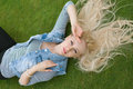 Blonde woman lying on the grass with untressed hair Royalty Free Stock Photo