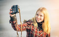 Blonde woman making self shot on her vintage retro camera happy smiling hipster lifestyle winter time Royalty Free Stock Photos