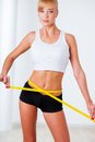 Blonde woman measuring her waistline beautiful with yellow tape Royalty Free Stock Photos