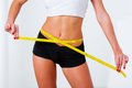 Blonde woman measuring her waistline with yellow tape photo without face Royalty Free Stock Photography