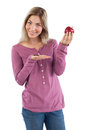 Blonde woman presenting an apple on a white background Royalty Free Stock Photo