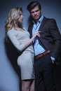Blonde woman pulling her man by his collar women men against studio background Royalty Free Stock Photography