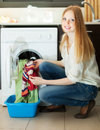 Blonde woman putting clothes in to machine smiling washing Royalty Free Stock Images