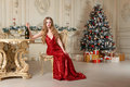 Blonde woman in red dress with glass of white wine or champagne siting on a chair in luxury interior. Christmas tree Royalty Free Stock Photo