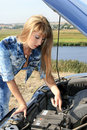 Blonde woman repairs car motor Royalty Free Stock Photography