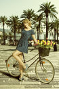 Blonde woman in sexy pose near bicycle girl wearing short blue dress sensual with colourful flowers the basket Royalty Free Stock Photography