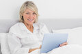 Blonde woman sitting in bed using tablet pc smiling at camera at home Royalty Free Stock Photo