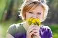 Blonde woman smell dandelion outdoors Stock Image