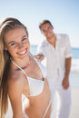 Blonde woman smiling at camera with boyfriend holding her hand women on the beach Royalty Free Stock Image