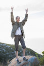 Blonde woman standing on a rock and cheering in the countryside Royalty Free Stock Images