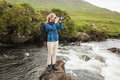 Blonde woman standing on a rock in a stream taking a photo the countryside Royalty Free Stock Photos