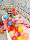 Blonde woman with sunglasses playing in her bath tube with bright colored balloons. Sensual girl with white red striped stockings Royalty Free Stock Photo