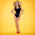 Blonde woman swimsuit wearing eyeglasses yellow background Stock Photos