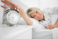 Blonde woman turning off alarm clock at home in bedroom Royalty Free Stock Photography