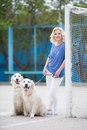 Blonde woman with two golden labrador retrievers outdoor. Royalty Free Stock Photo