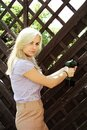 Blonde woman using a drill young blond to repair wooden fence Stock Image