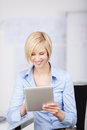 Blonde woman using tablet pc sitting in the office Royalty Free Stock Photos