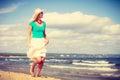 Blonde woman wearing dress walking on beach