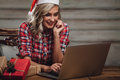 Blonde woman wearing santa hat, working with laptop Royalty Free Stock Photo
