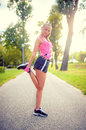 Blonde woman working out, exercising and stretching in park Royalty Free Stock Photo