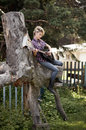 Blonde young country girl sitting on large old stump and playing the guitar Stock Photography