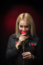Blonde young smiling woman smelling red rose Royalty Free Stock Photo