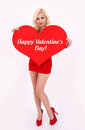 Blonde young woman holding red heart with words Happy Valentines' day Royalty Free Stock Images