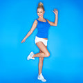 Blonde young woman wearing canvas shoes blue background Stock Images