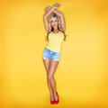 Blonde young woman yellow background Stock Photography
