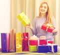 Blondie girl sitting at table with many presents in boxes