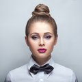 Blondie woman in white shirt and black bow tie young over Stock Images