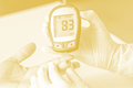 Blood glucose meter the blood sugar value is measured on a fing finger processed in tinted in orange tone Stock Photos