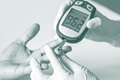Blood glucose meter the blood sugar value is measured on a fing finger processed in tinted photo in brown tone Stock Photos