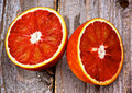 Blood oranges halves of ripe raw orange closeup on rustic wooden background Royalty Free Stock Images