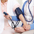 Blood pressure measurement in nursing home on senior woman Stock Photo