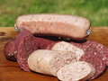 Blood sausage and liver sausage on a bed of oak Stock Photos