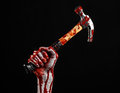 Bloody halloween theme: bloody hand holding a bloody hammer isolated on a black background Royalty Free Stock Photo
