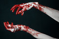 Bloody hands in white gloves a scalpel a nail black background zombie demon maniac studio Royalty Free Stock Image