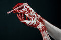 Bloody hands in white gloves a scalpel a nail black background zombie demon maniac studio Royalty Free Stock Photos