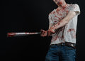 Bloody topic the guy in a bloody t shirt holding a bloody bat on a black background studio Stock Photography