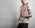 Bloody topic the guy in a bloody t shirt holding a bloody bat on a white background studio Royalty Free Stock Photography