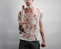 Bloody topic the guy in a bloody t shirt holding a bloody bat on a white background studio Royalty Free Stock Image