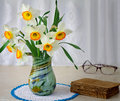 Blossoming narcissuses in a vase on a table beautiful large flowers of near the ancient book Stock Images